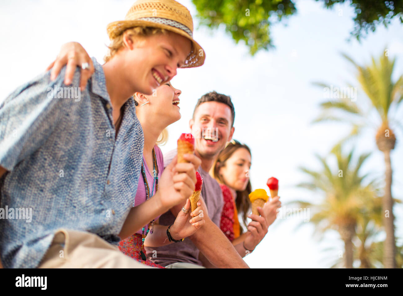 Cuatro amigos adultos riendo y comiendo conos de helado, Mallorca, España Foto de stock