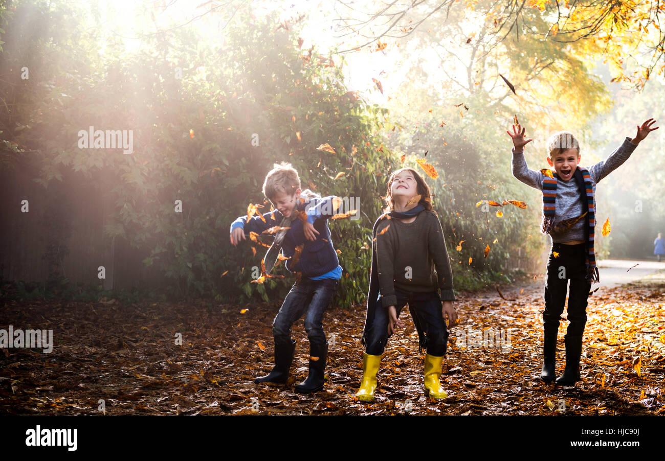 Tres jóvenes, jugar afuera, arrojando hojas de otoño Imagen De Stock