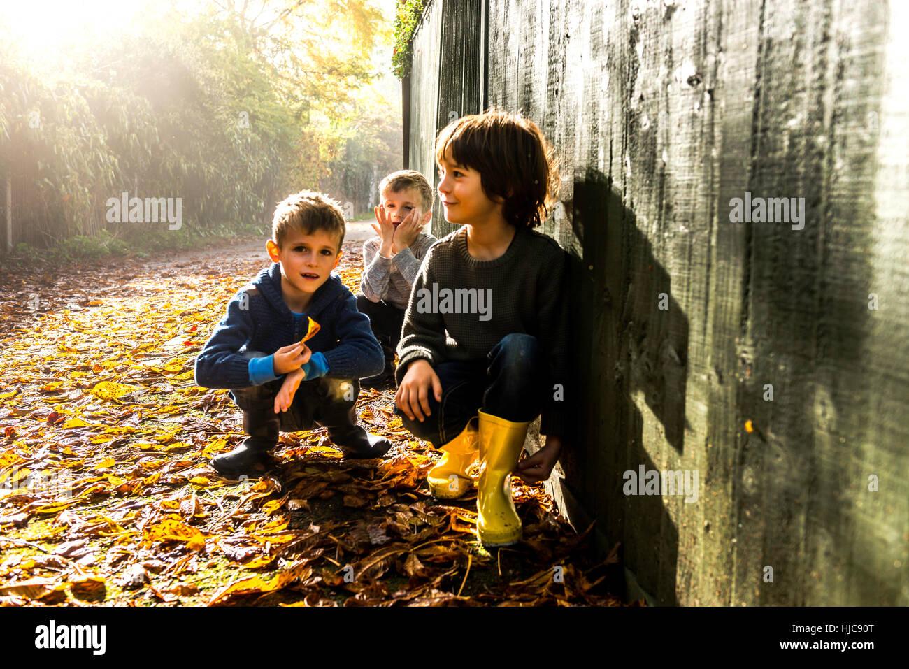 Tres jóvenes, sentados contra la valla, rodeado por hojas de otoño Imagen De Stock