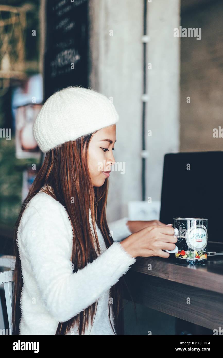 Hermosa joven bebiendo té en el café Imagen De Stock