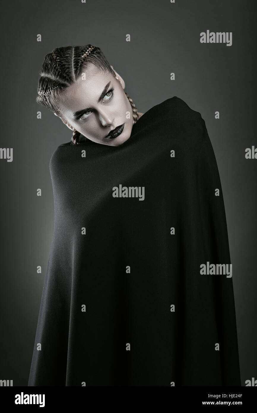 Mujer vampiro envuelto en manto negro . Halloween y horror Imagen De Stock
