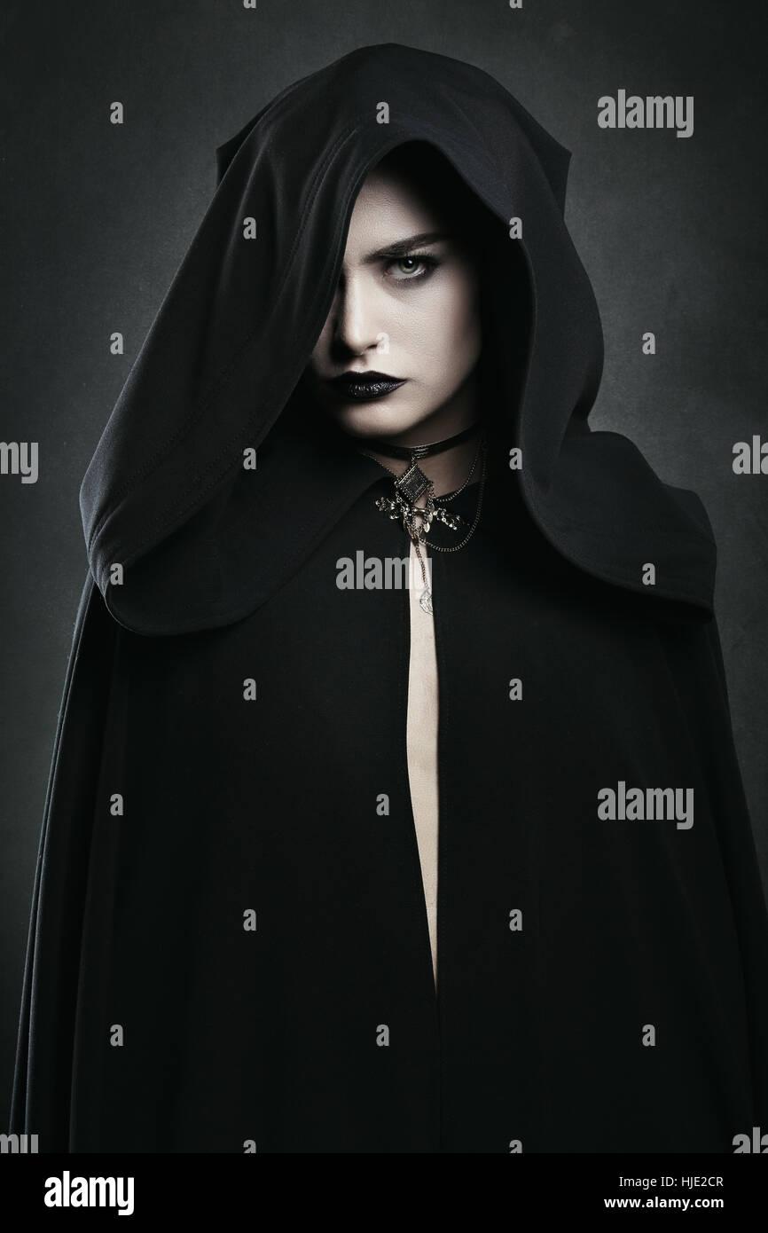 Hermosa mujer vampiro con manto negro . Halloween y horror Imagen De Stock