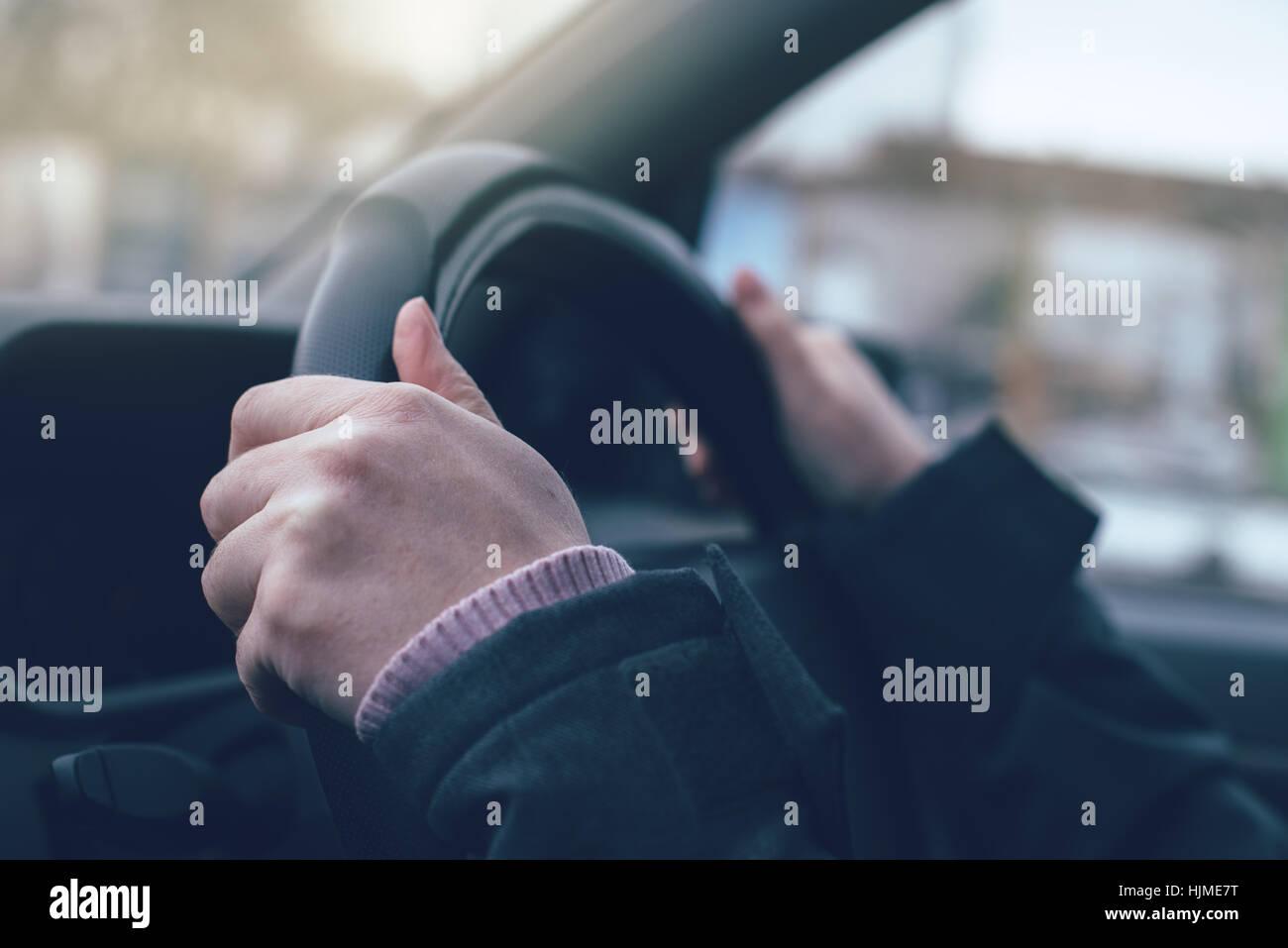 Manos femeninas se agarra al volante de un coche, junto con el enfoque selectivo Imagen De Stock
