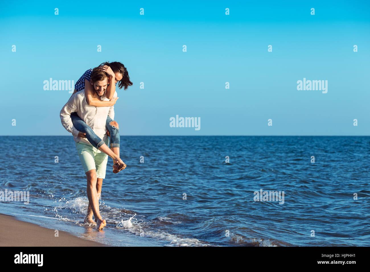 Guapo dando piggy back a su novia en la playa. Imagen De Stock