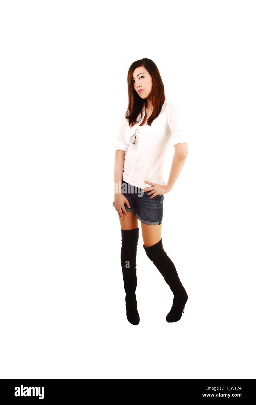 db3c62794 Una joven china muy altos para fondo blanco permanente en negro botas  largas y pantalones cortos.