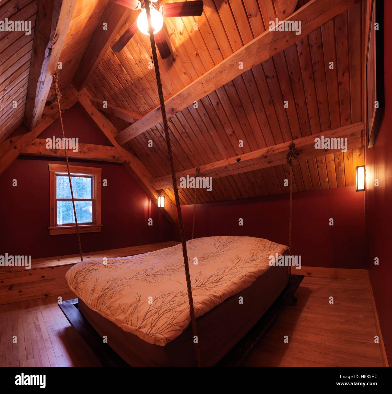 Ático Loft dormitorio con una cama colgante en un bastidor de madera canadiense Country House, interior con Imagen De Stock
