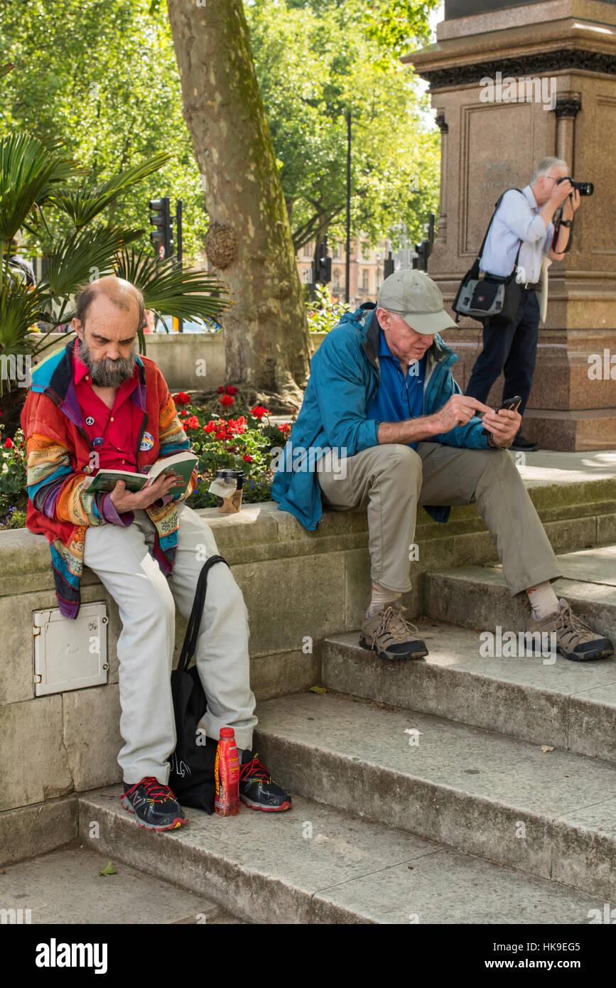 Tres hombres al lado de la Plaza del Parlamento. Uno está leyendo un libro, otro mirando su teléfono y Imagen De Stock
