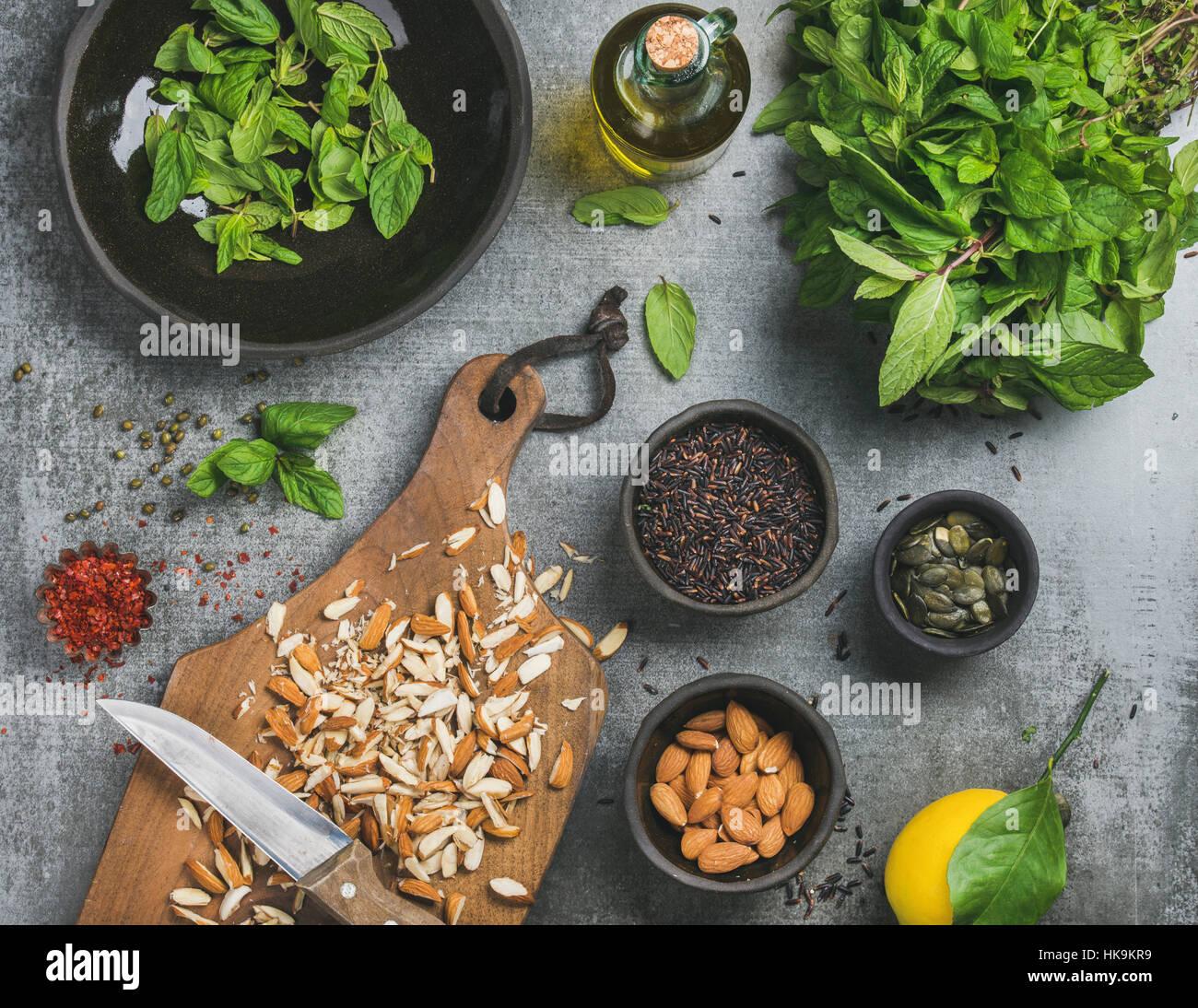 Saludable, vegetariano o vegano comer limpio ingredientes de cocina. Almendras picadas, menta fresca, aceite, arroz Imagen De Stock
