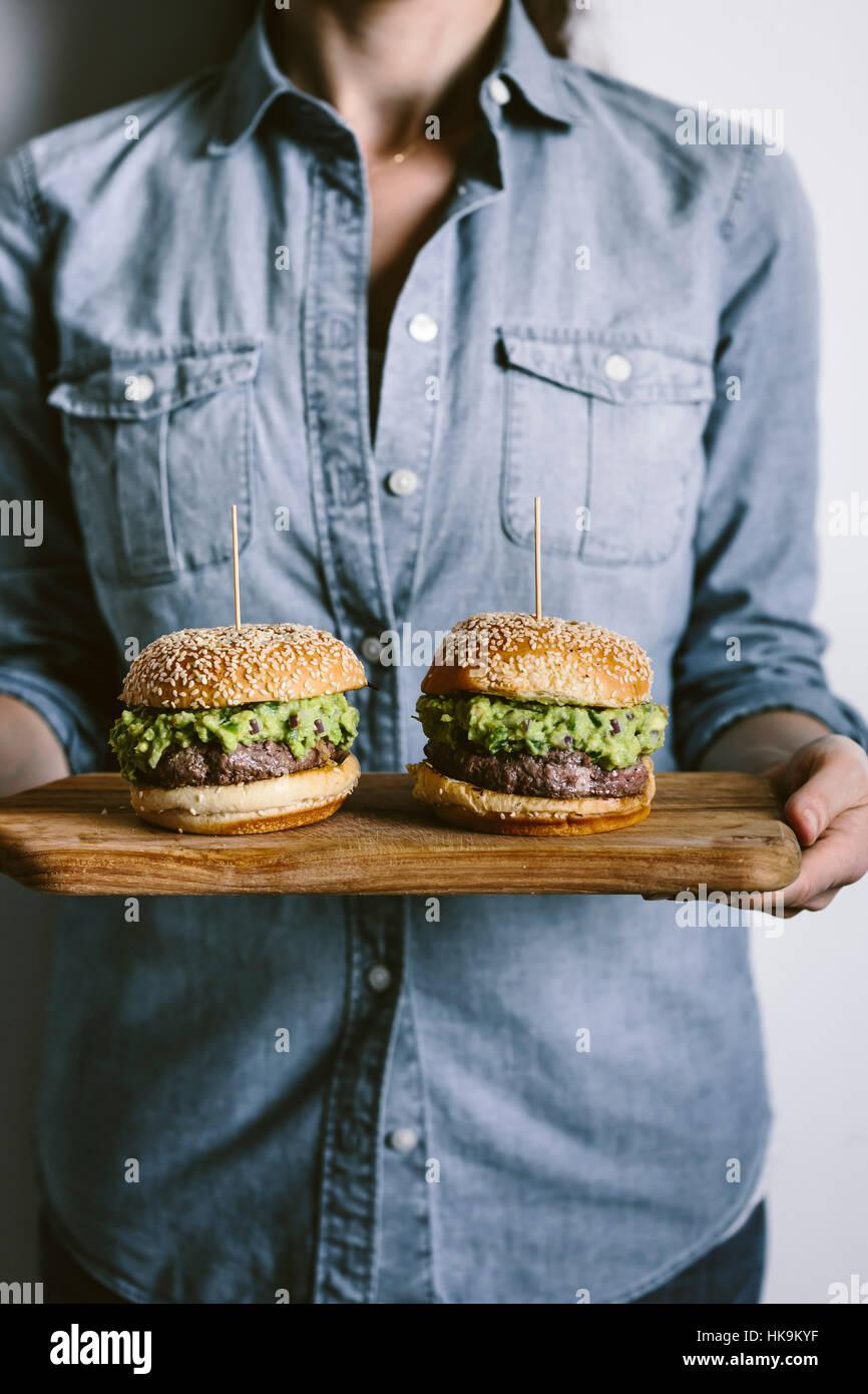 Una mujer es fotografiada desde la vista frontal manteniendo dos guacamole hamburguesas en sus manos sobre una tabla Imagen De Stock