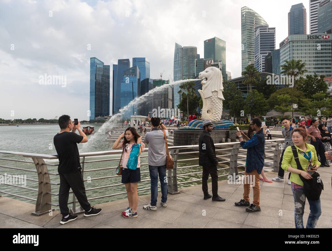 Singapur, Singapur - 22 de febrero de 2016: Los turistas toman fotos en frente de la ciudad famosos rascacielos y la estatua Merlion. Foto de stock