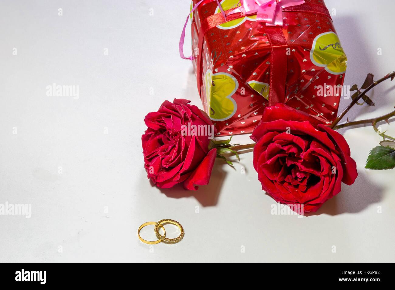 Rosas de color rojo brillante con anillos de compromiso de oro y envuelto don elemento aislado en blanco. El espacio Imagen De Stock