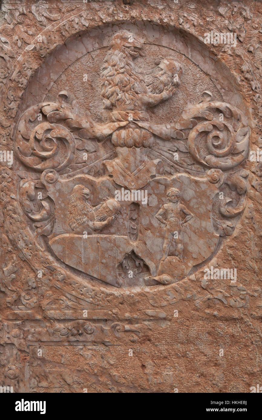 León que sostiene una cabeza humana. Detalle de la lápida en la Iglesia de San Pedro (Alter Peter) en Imagen De Stock