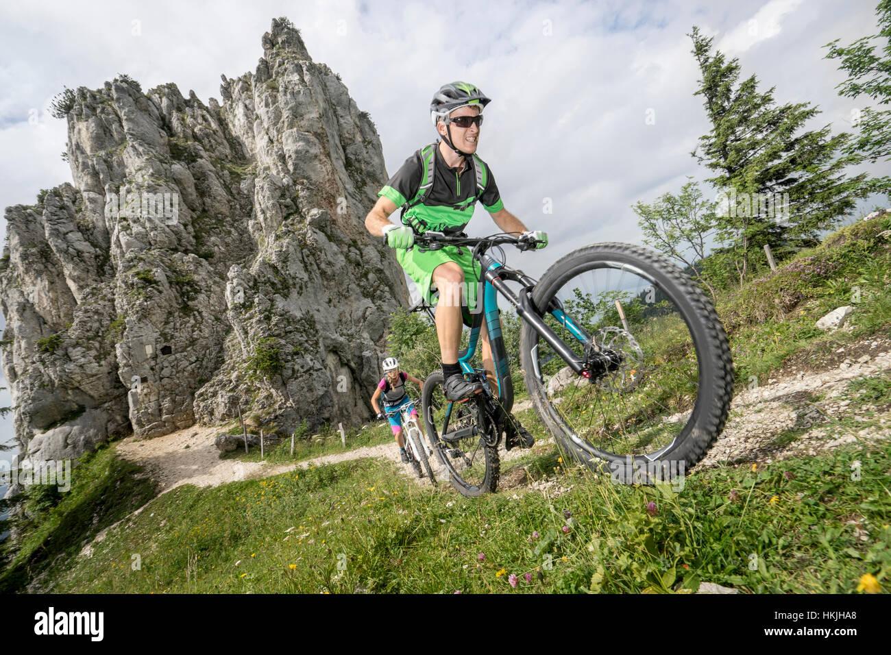 Los ciclistas de montaña en bicicleta cuesta arriba en la naturaleza, Kampenwand, Baviera, Alemania Imagen De Stock