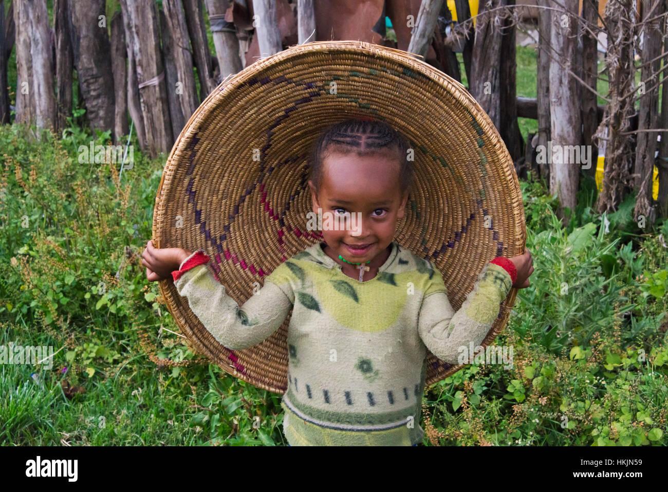 Kid vistiendo la tapa del contenedor de pan plano injera, Addis Ababa, Etiopía Imagen De Stock