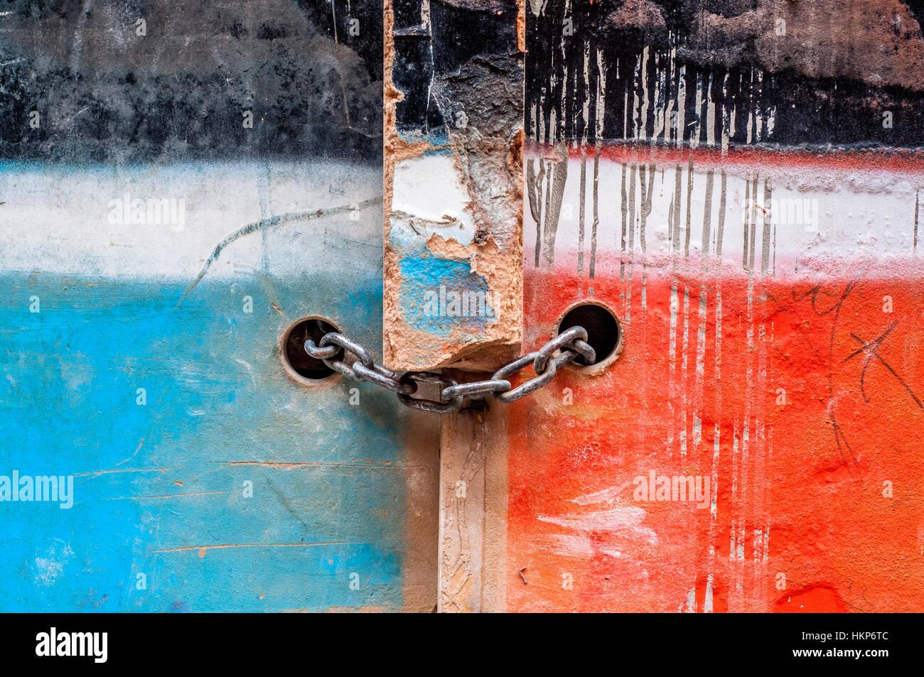 Cadena con candado en una antigua puerta de madera pintada de dos colores, azul y rojo Foto de stock