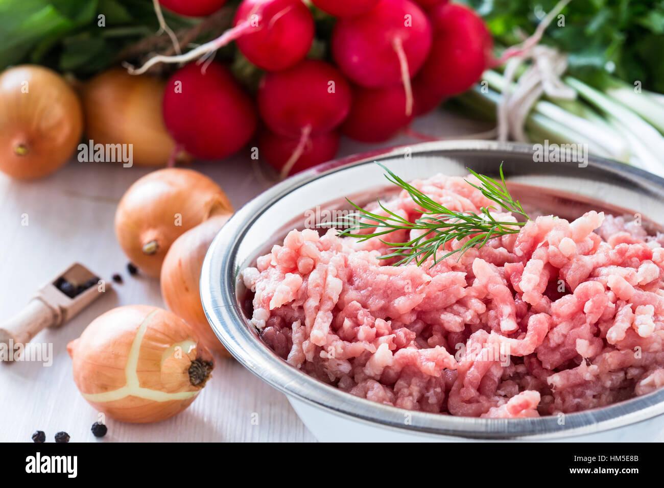 La carne molida cruda en blanco tazón. La carne picada de cerdo sobre un fondo de hortalizas frescas orgánicas Imagen De Stock