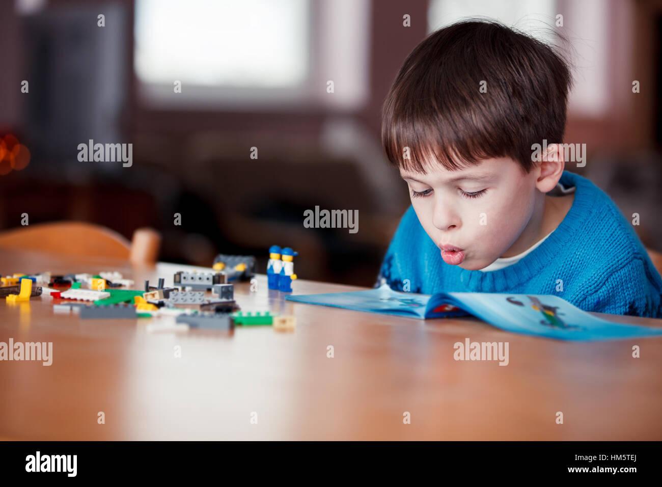 Concentrado niño leer un manual Foto de stock