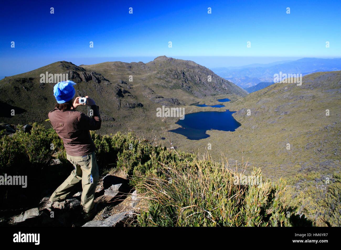 Turista mirando el Lago Chirripó desde la cumbre del Monte Chirripó, la montaña más alta de Imagen De Stock