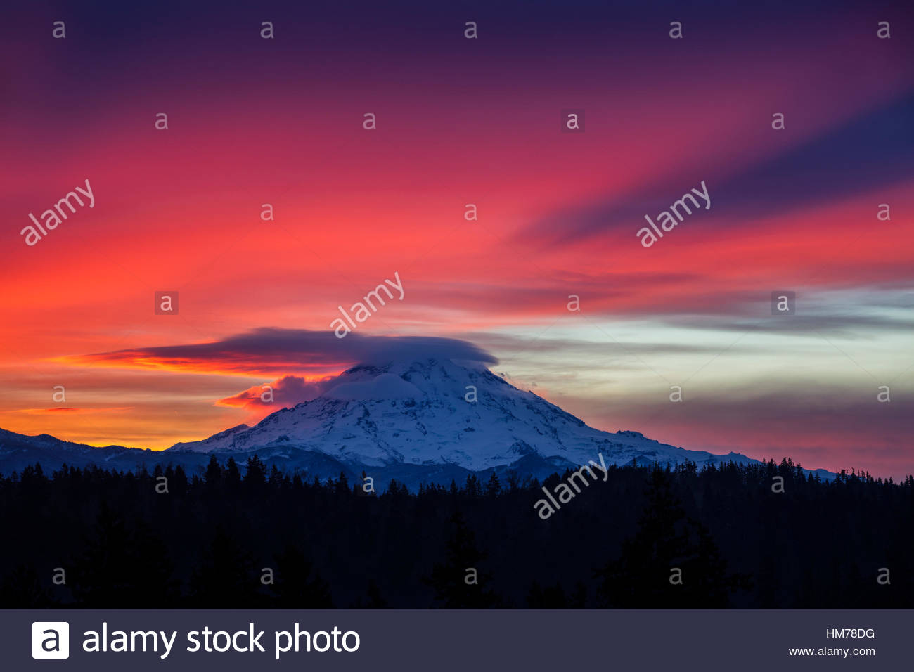Al amanecer, el Monte Rainier proyecta su propia sombra sobre una capa de nubes cirrostratus en esta vista del lago Imagen De Stock
