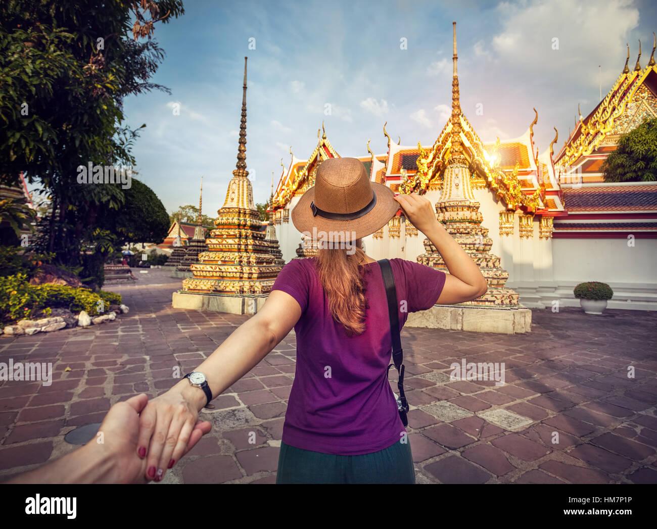 Mujer con sombrero y camiseta púrpura hombre principal con la mano al famoso templo Wat Pho en Bangkok, Tailandia. Imagen De Stock
