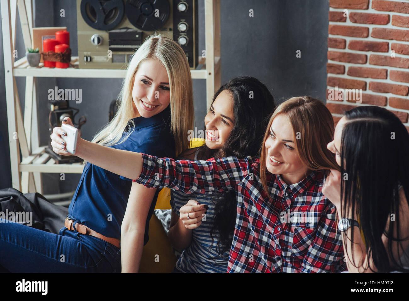 Cuatro hermosa joven haciendo selfie en un café, mejores amigos niñas junto a divertirse, planteando el Imagen De Stock