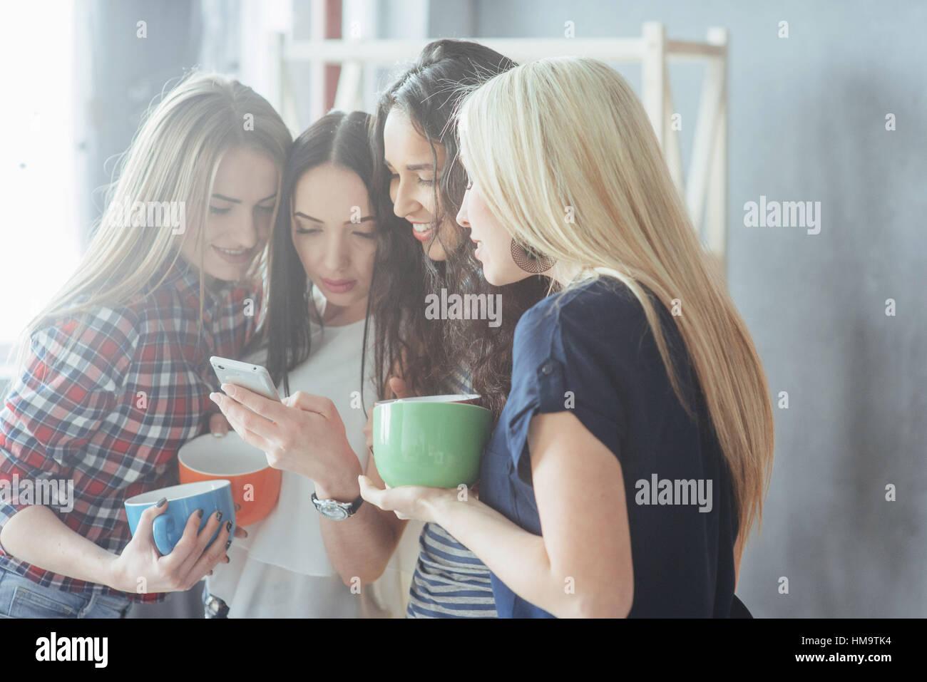 Grupo bellos jóvenes disfrutando en la conversación y beber café, mejores amigos niñas junto Imagen De Stock