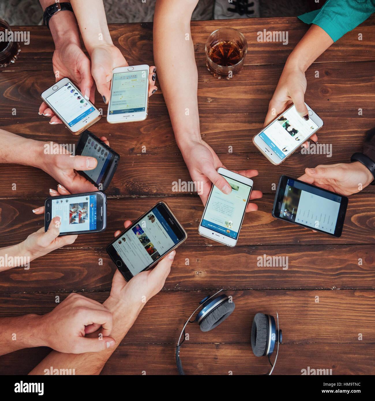Vista superior del círculo de manos utilizando el teléfono en cafe - amigos multirracial adicto móvil Imagen De Stock