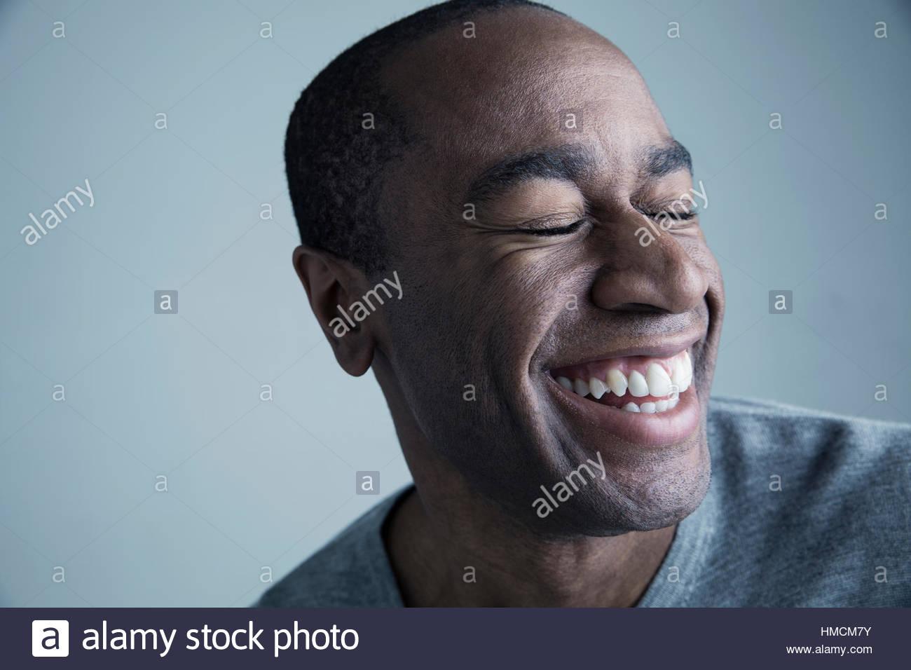 Retrato hombre afroamericano sonriendo con los ojos cerrados Imagen De Stock