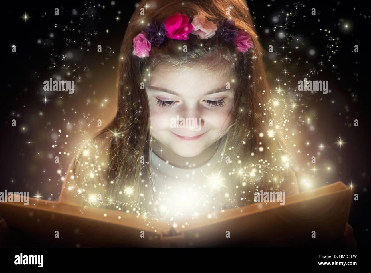 Niña leyendo libro mágico, concepto de fantasía Foto de stock