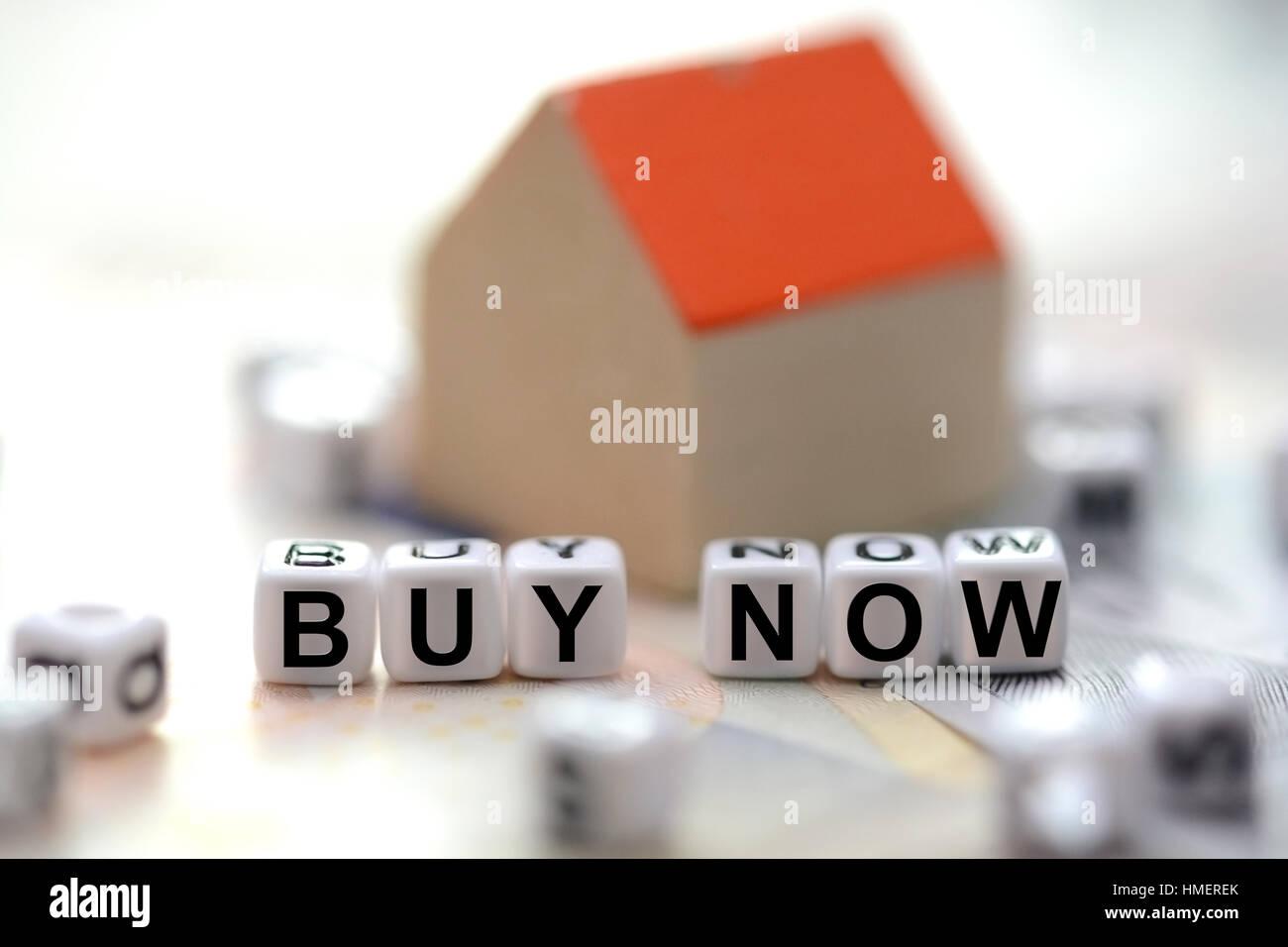 Comprar ahora texto escrito con letra de azulejos abalorios y un pequeño modelo borrosa en el fondo de la casa Foto de stock