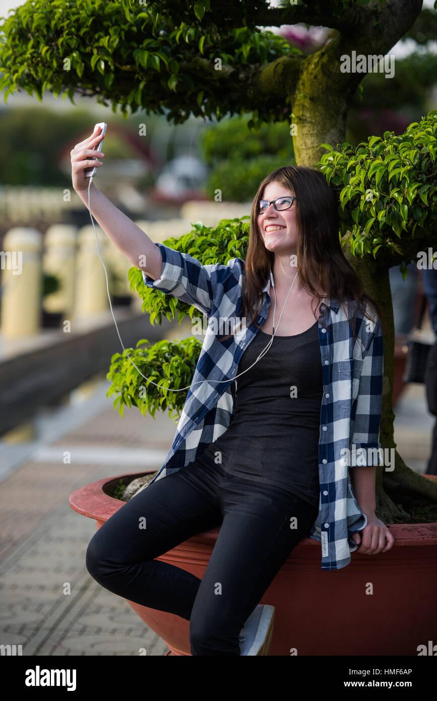 3df9d8fa42 Hermosa chica adolescente vistiendo negro pantalones vaqueros y camisa a  cuadros teniendo un selfie en smartphone al aire libre en el parque