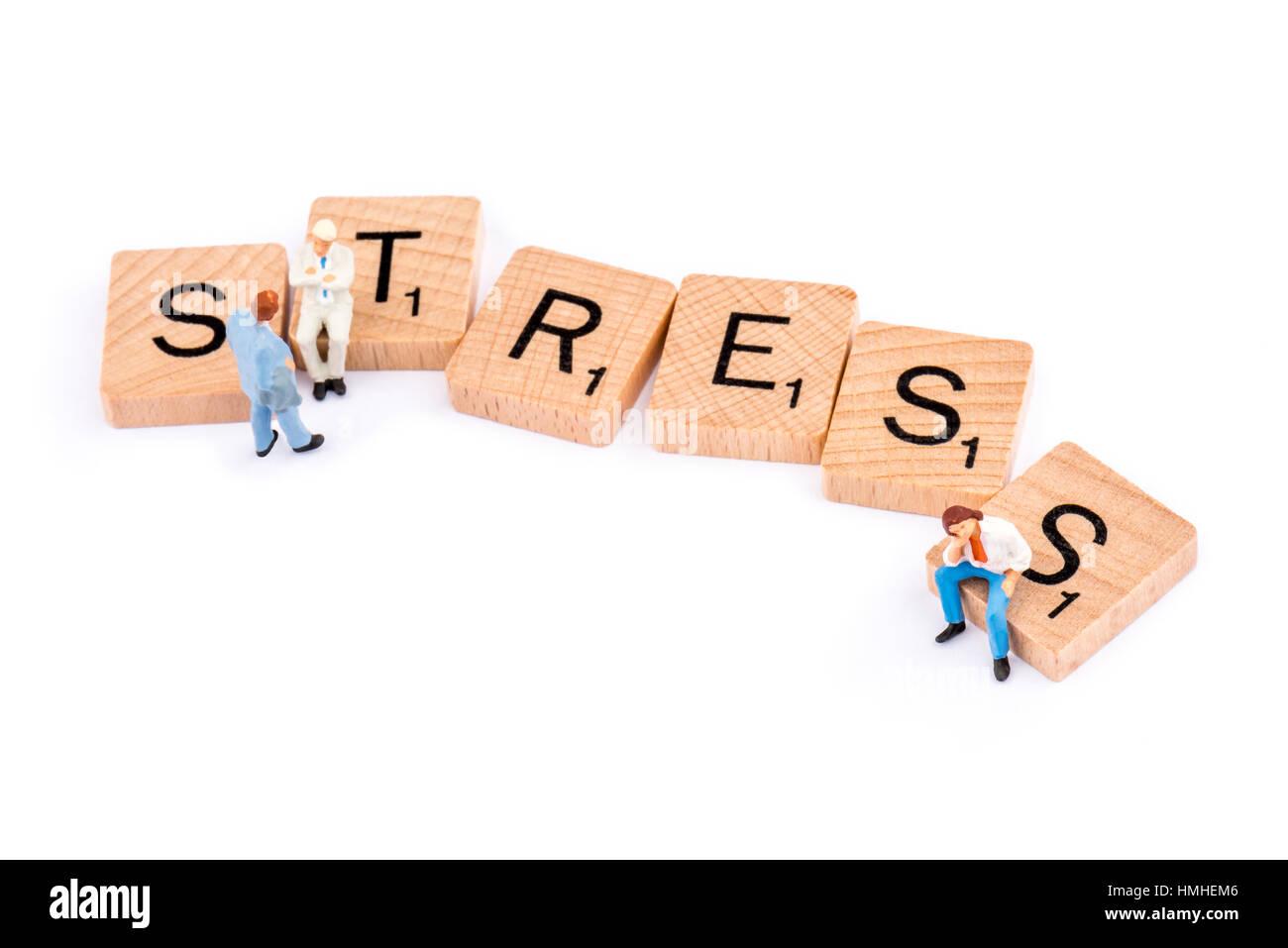 Scrabble letras componen la palabra estrés dos figuras ignorar un hombre joven sentado en la letra S. Imagen De Stock