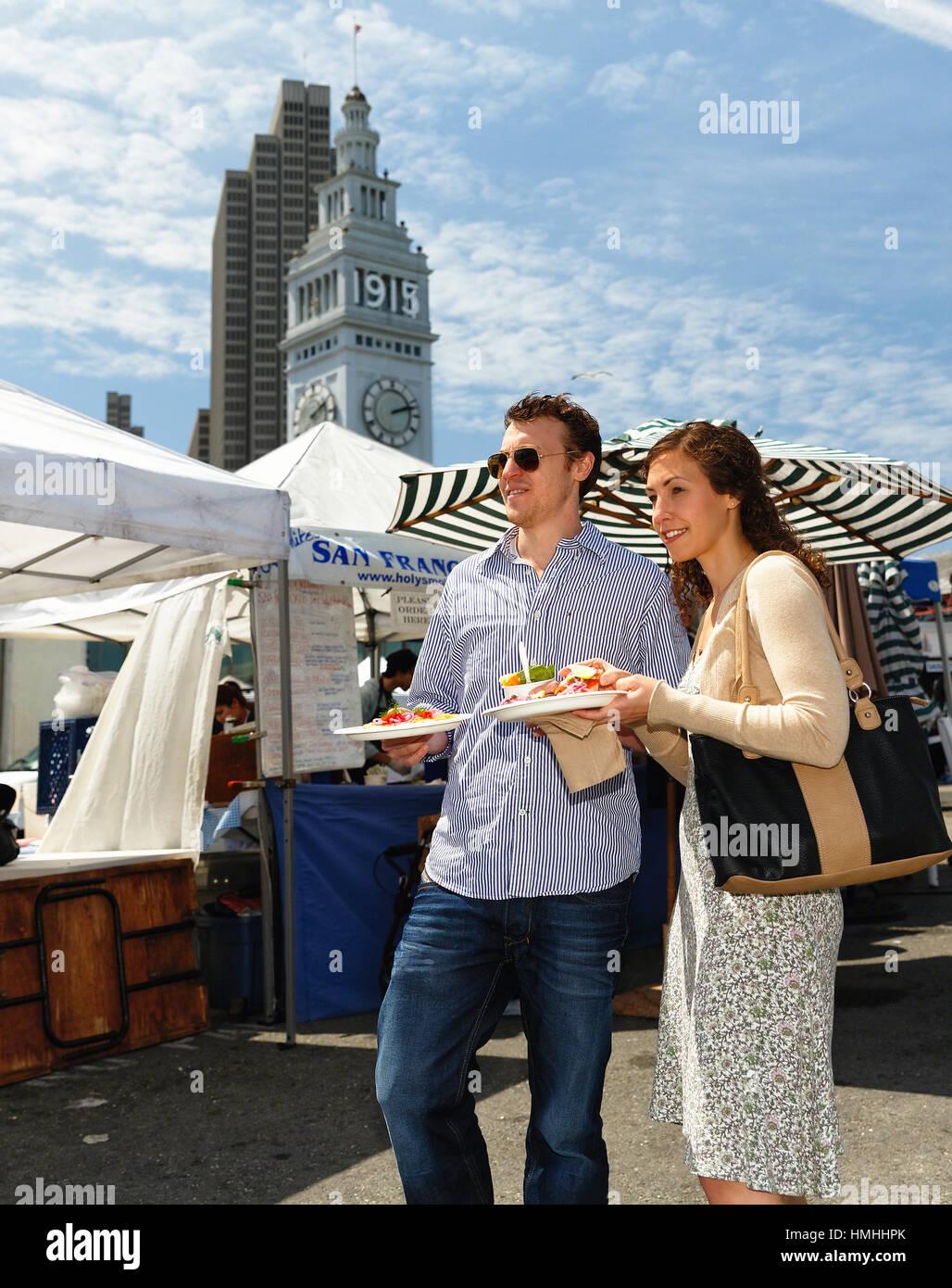 Ángulo de visión baja de una pareja en una feria de la calle con comida paseos, San Francisco, California Imagen De Stock