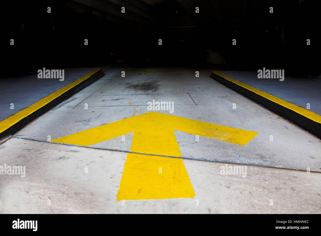 Flecha amarilla en la acera que conduce a la oscuridad Imagen De Stock