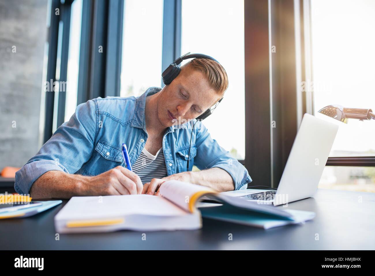 Foto de joven estudiando en la biblioteca de la universidad sentado en la mesa con el portátil y los libros. Imagen De Stock
