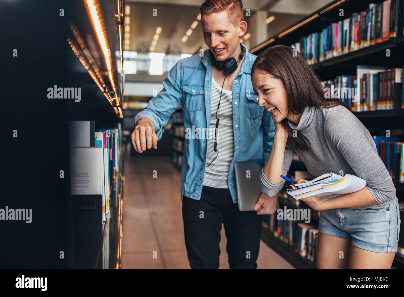 Imagen de hombre joven y feliz mujer de pie por la estantería de libros en la biblioteca y busca libros. Biblioteca Imagen De Stock