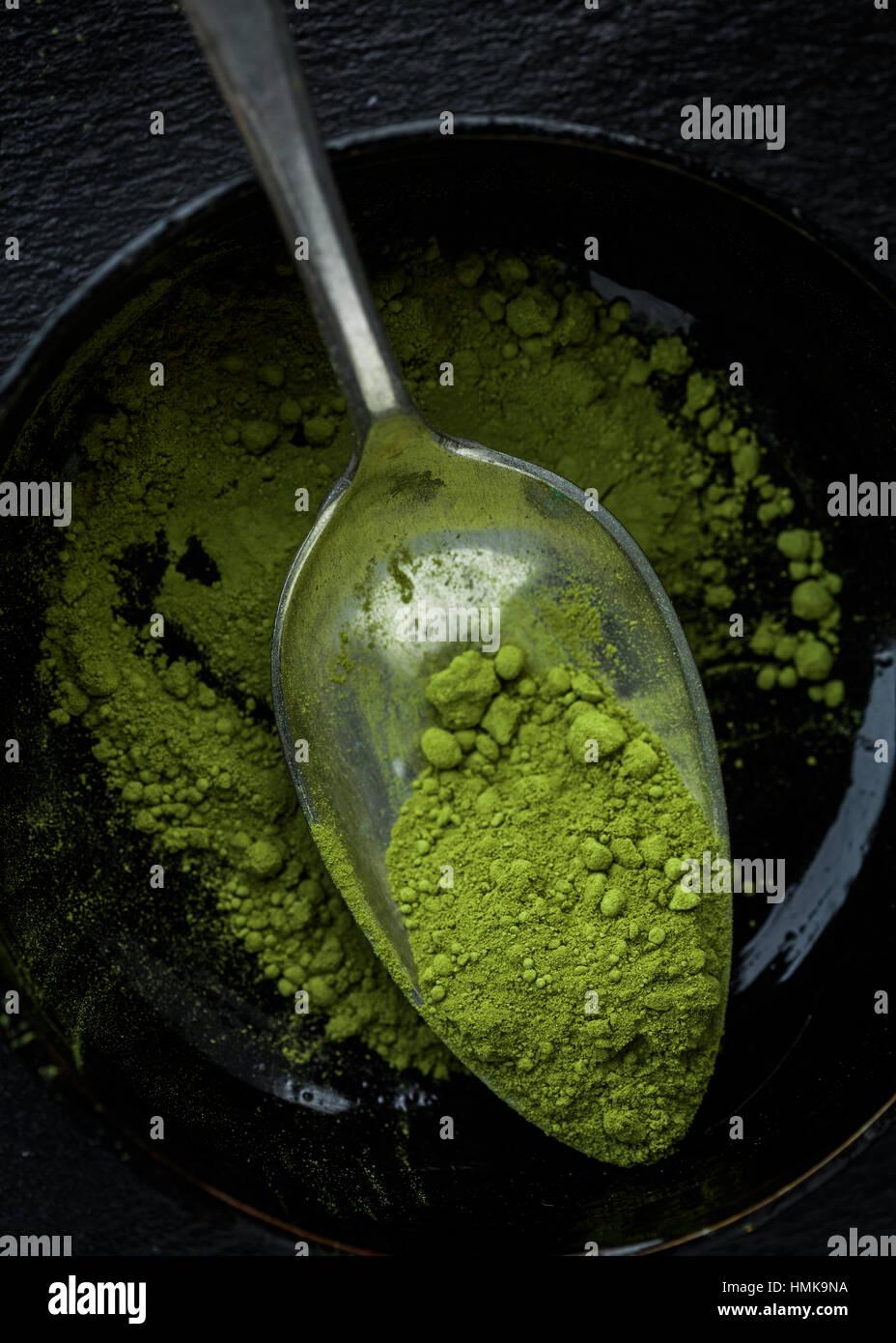 Una taza de té matcha en polvo en una cuchara Foto de stock