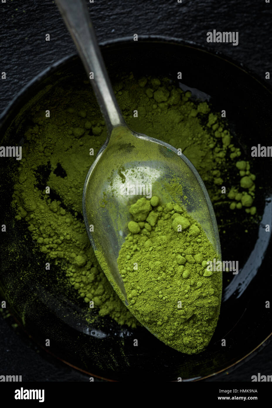 Una taza de té matcha en polvo en una cuchara Imagen De Stock