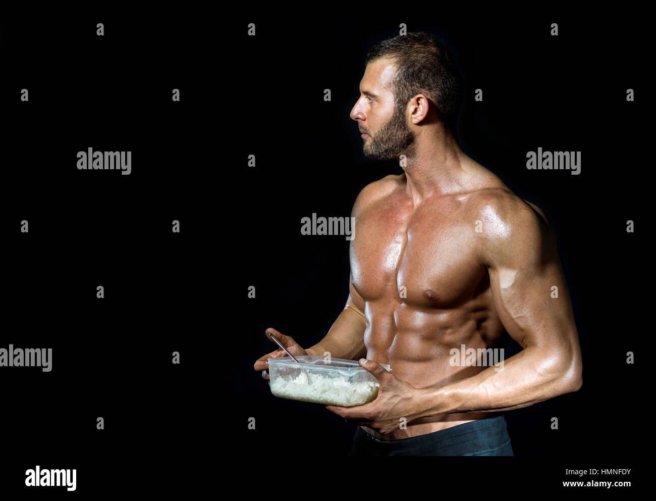 Colocar adulto joven culturista muscular sano comer arroz blanco del plato de plástico aislado. Imagen De Stock