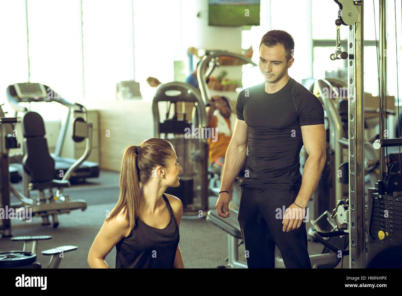 Macho joven entrenador personal habla a la clienta y dándole consejos para la motivación. Imagen De Stock