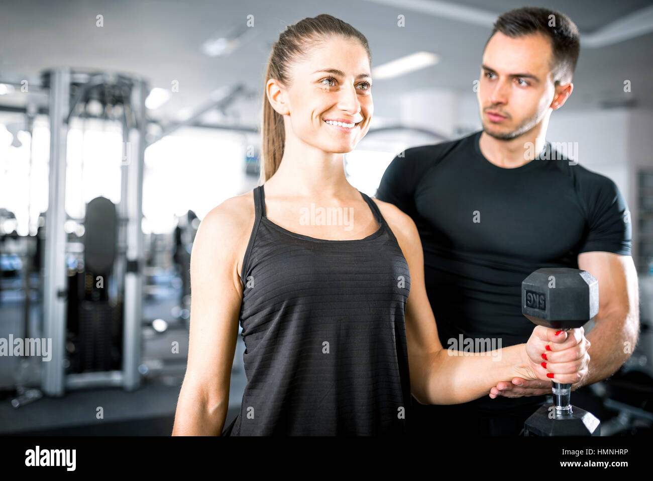 Adulto joven mujer trabajando en el gimnasio, haciendo flexiones de brazos (bíceps) con la ayuda de su entrenador personal. Foto de stock