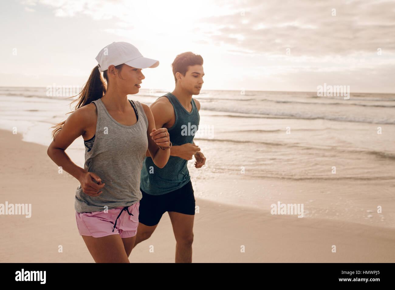 Pareja joven correr juntos en la playa. Disparó al aire libre de la joven pareja a correr por la mañana. Foto de stock