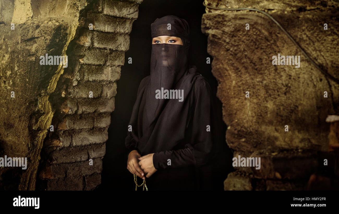 TAIPING, Perak - 6 de agosto de 2016 : Un niqab o burqa chica de pie con el rosario en la mano enfrente de una cueva. Imagen De Stock