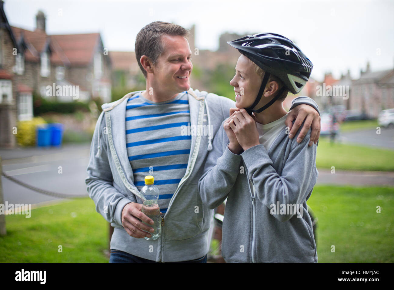 Padre e hijo preparándose para su bicicleta. El padre tiene su brazo alrededor de su hijo y están sonriendo Imagen De Stock