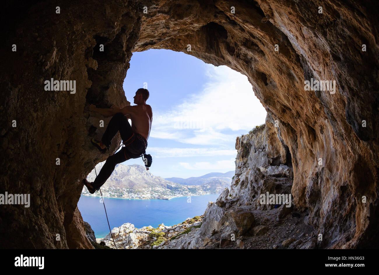 Joven subiendo a lo largo de rocas Foto de stock
