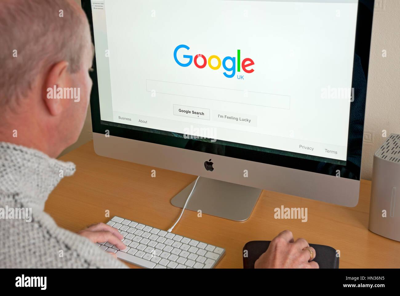 El hombre busca en Google UK homepage en la pantalla de ordenador. Imagen De Stock