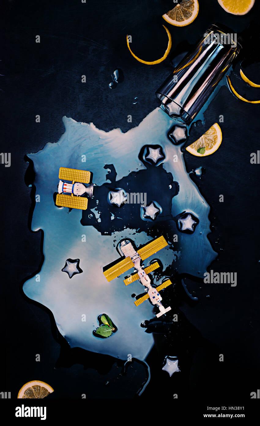 Un galass de derrame de galaxia con estrellas de hielo y las estaciones espaciales Imagen De Stock
