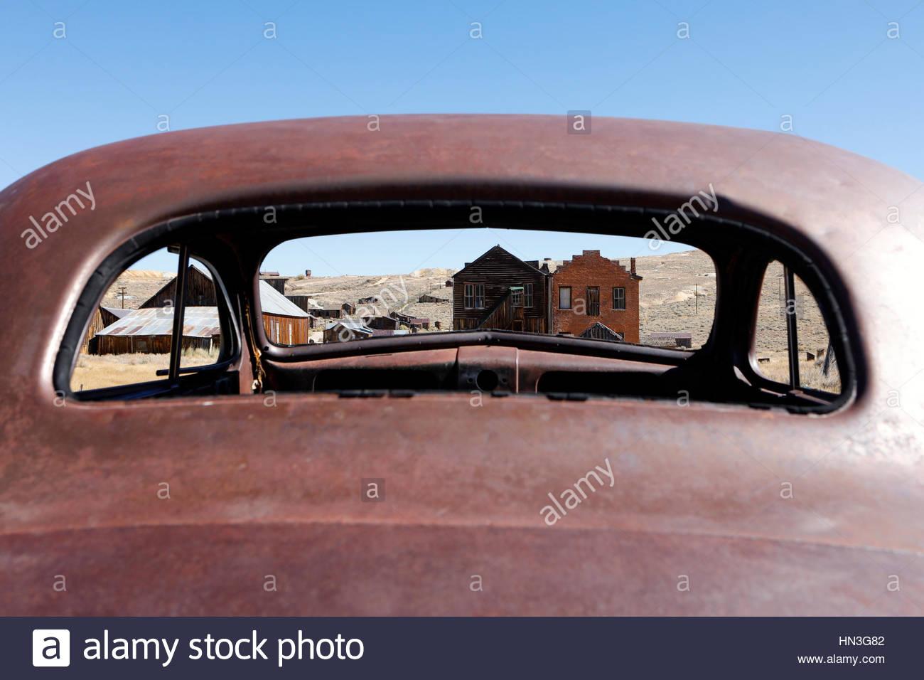 Edificios abandonados a través de la ventana de un coche viejo en la ciudad fantasma de Bodie. Imagen De Stock