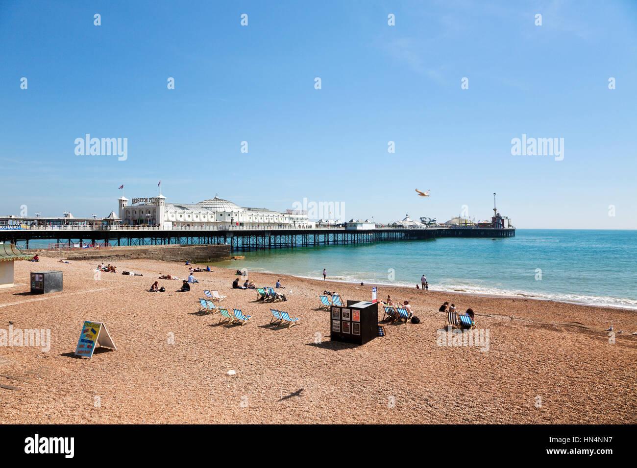 Brighton, Sussex, Reino Unido - 16 de mayo de 2014: Los turistas relajándose en la playa junto al embarcadero Imagen De Stock