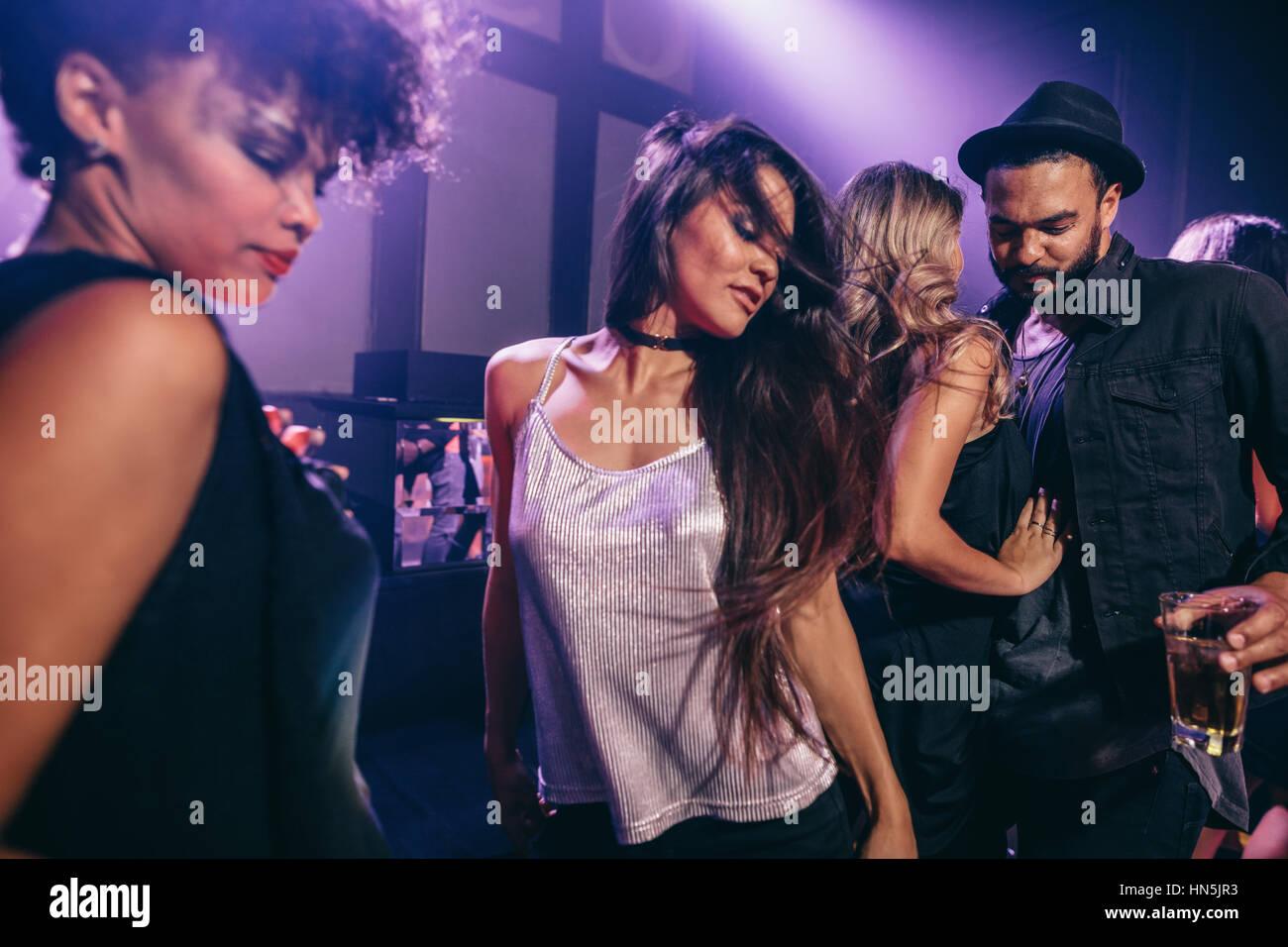 Mujer joven bailando en parte con amigos cercanos. Grupo de jóvenes divirtiéndose en la discoteca. Imagen De Stock